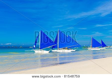 Sailboats With Blue Sails On A Tropical Beach. Journey And Summer Vacation Concept