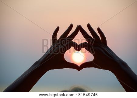 Heart shape make by hands and sea sunset.