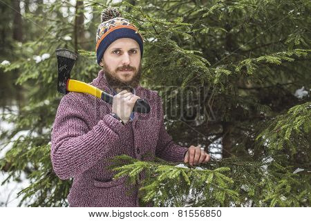 Lumberjack near the christmas tree in forest