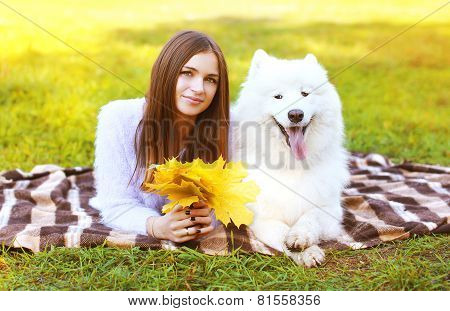 Happy Pretty Woman And White Samoyed Dog Having Fun Outdoors On The Grass