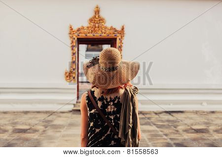 Woman Looking At Door To Buddhist Temple