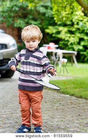 Little Cute Funny Kid Boy Playing Badminton In Domestic Garden