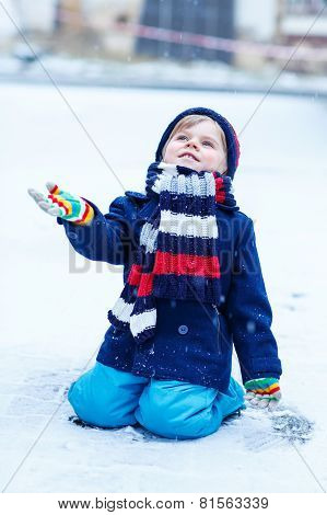 Cute Little Funny Boy In Colorful Winter Clothes Having Fun With