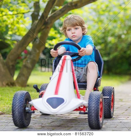 Active Little Boy Having Fun And Driving Toy Race Car