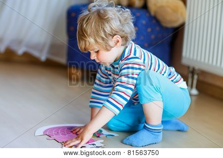 Little Cute Blond Boy Playing With Puzzle Game At Home