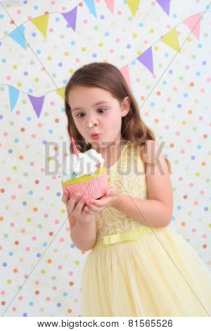 Child holding a birthday cake