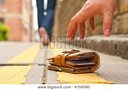 guy picking up a lost a lost purse/wallet
