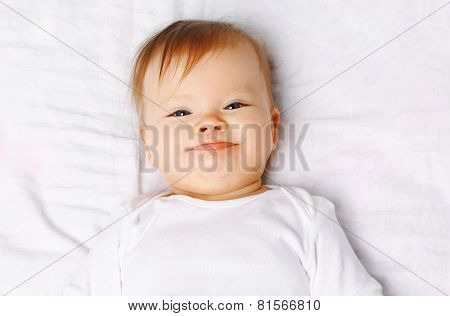 Closeup Portrait Cute Positive Baby On The Bed, Top View