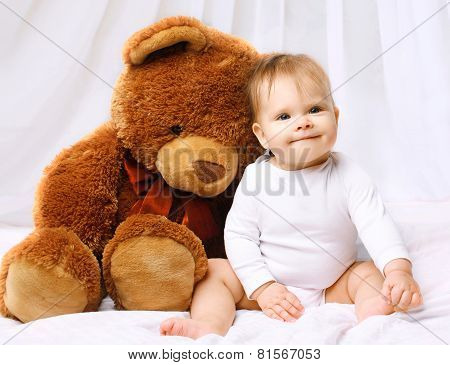 Smiling Baby Playing With Teddy Bear On The Bed Home