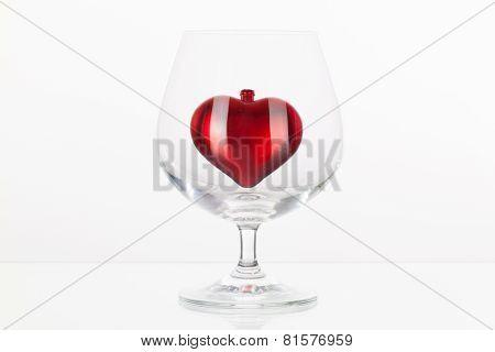 Red Heart Inside A Glass Of Cognac