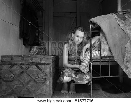 portrait of sad bloond beautiful girl sitting on the floor in small room near the bed and chest. bla
