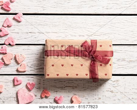 Vintage gift box with heap of small hearts on white wooden background.
