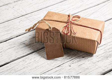 Gift box with blank gift tag on white wooden background.