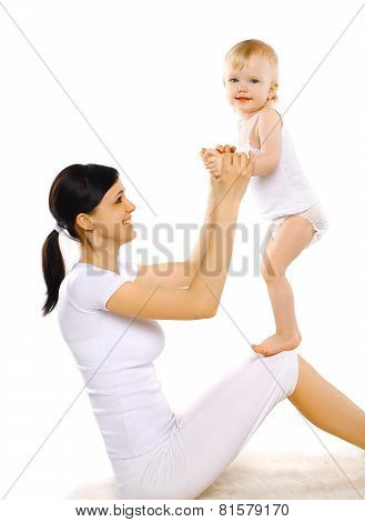 Sport, Active, Leisure And Family Concept - Happy Mom And Baby Doing Exercise Having Fun
