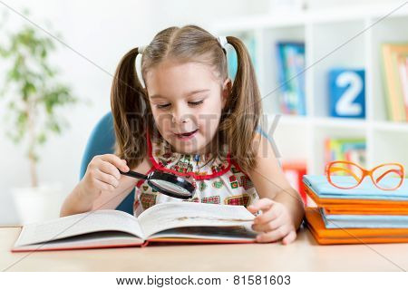 Astonished kid looking through a magnifying glass with book