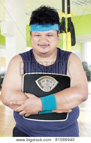 Overweight Person With Scale In Fitness Center