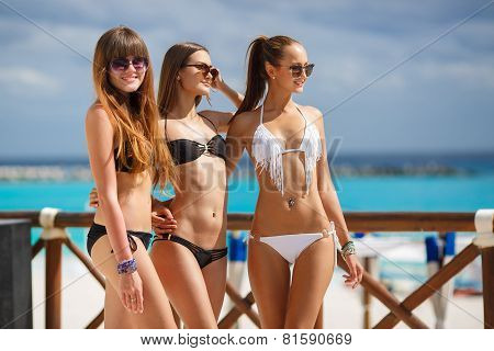 Beautiful girls in bikini relax poolside at the ocean background.