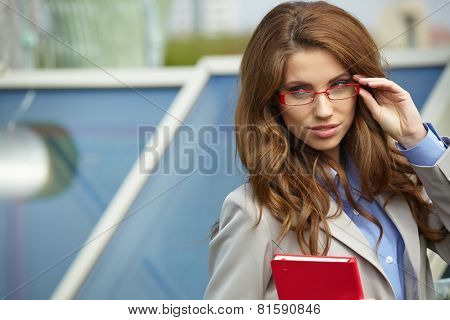 Young businesswoman (real estate agent) presenting detached modern houses