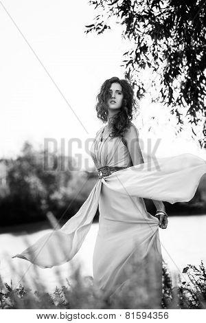 Female Model In Long Beige Dress Posing Dynamic In The Beach. Waving Fabric. Fluttering Long Skirt