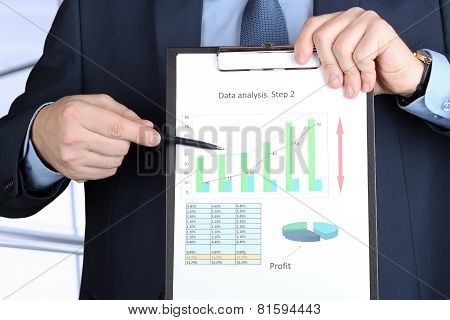 Young Businessman Showing Graphs By Pen