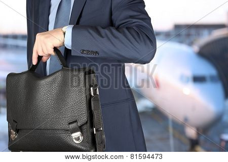 Businessman Checking Time On His Watch . Airplane Behind