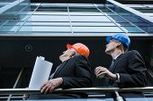 stock photo of supervision  - Image of engineers in helmets supervising construction site - JPG