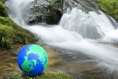 image of northern hemisphere  - Earth model on moss in front of brook  - JPG