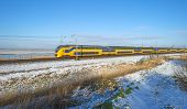pic of passenger train  - Passenger train in a snowy landscape in winter - JPG