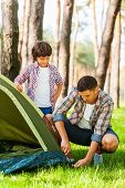 stock photo of tent  - Cheerful father and son pitching a tent while camping in the forest together - JPG