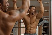 image of abdominal muscle man  - Muscular Man Flexing Abdominal Muscles Abs In A Health Club - JPG