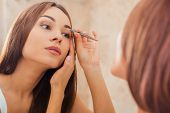 picture of raised-eyebrow  - Beautiful young woman tweezing her eyebrows while looking at the mirror - JPG