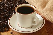 picture of brew  - A cup of fresh brewed coffee with dark roasted coffee beans in the background - JPG