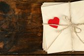 stock photo of revelation  - Stack of love letters on rustic wooden planks background - JPG