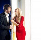 stock photo of girl next door  - Attractive couple standing next to a white door - JPG