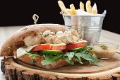 foto of rocket salad  - Healthy wheat sandwich burger with BBQ grilled chicken steak cheese tomato rocket salad cucumber fried potato and mustard sauce served for eating on wooden board - JPG