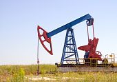 foto of nonrenewable  - Oil field Pump Jack with a bright blue sky - JPG
