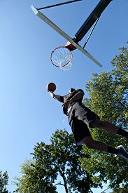 image of slam  - Young basketball player driving to the hoop for a high flying slam dunk - JPG