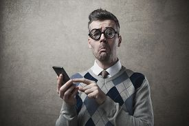 foto of nerd glasses  - Funny clueless dumb guy having troubles with his smartphone - JPG