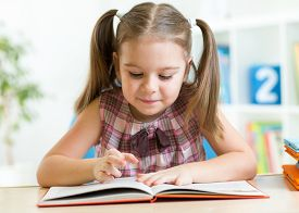 foto of big-girls  - Child girl reading story from big book in nursery - JPG