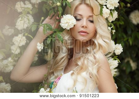 Beautiful woman in summer Park near the Bush blooming roses