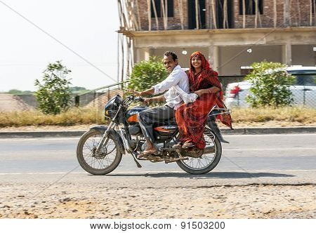 Couple Riding On Scooter Through Busy Highway Street