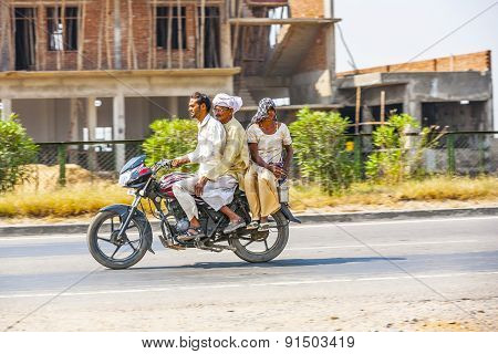 Mother, Father And Son Riding On Scooter Through Busy Highway