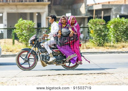 Man With Mother And Wife Riding On Scooter On The Highway