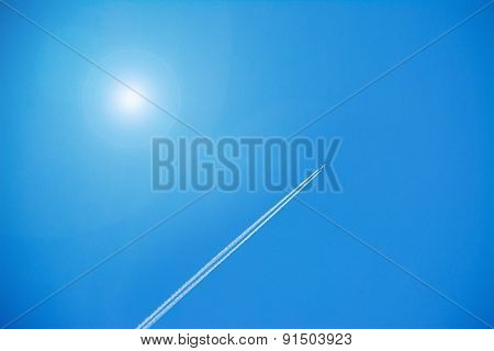 Airplane Contrails Under A Shining Sun