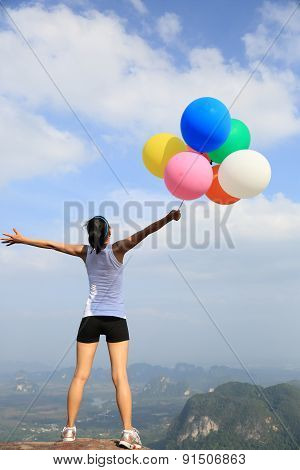 young asian woman with colored balloons