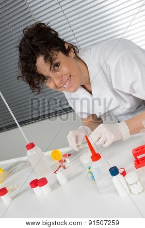 Laboratory assistant inserting laboratory glass bottle