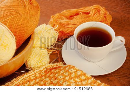 Woolen Yarn, Knitting And Cup Of Tea On Wooden Background.