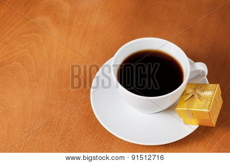 White Coffee Cup And Gold Gift Box With Bow On Wooden Background