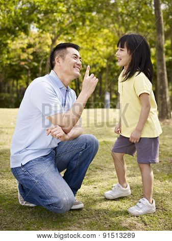 Asian Father And Daughter Having Fun In Park