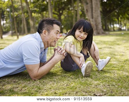 Asian Father And Daughter Having A Conversation In Park